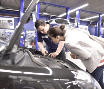 Mécanicien expliquant ce qu'il fait à la voiture d'une jeune femme